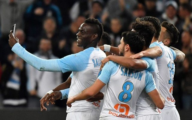 Marseille's Italian forward Mario Balotelli (L) takes a selfie with teammates after scoring during the French L1 football match between Olympique de Marseille and AS Saint-Etienne at the Velodrome Stadium in Marseille, southern France on March 3, 2019. (Photo by GERARD JULIEN / AFP)