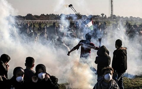 A Palestinian uses a slingshot to fling back a tear gas canister thrown by Israeli forces during clashes at the fence along the border with Israel, east of Gaza City, on March 8, 2019. (Mahmud Hams/AFP)