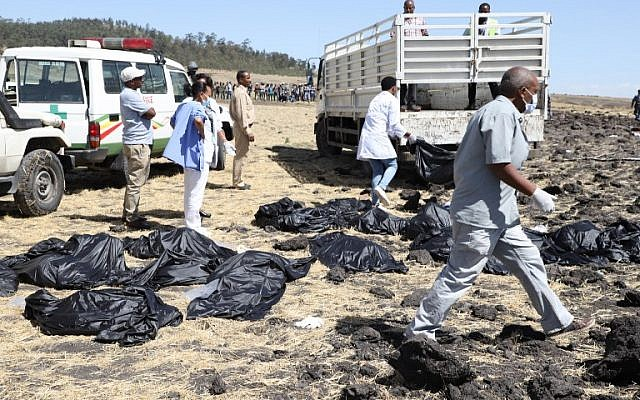 Rescue team walk past collected bodies in bags at the crash site of Ethiopia Airlines near Bishoftu, Ethiopia, on March 10, 2019. (Michael TEWELDE/AFP)