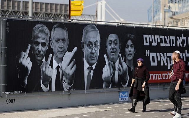 A picture taken on March 11, 2019, shows Israelis walking past a campaign poster for the Yashar political party, showing Prime Minister Benjamin Netanyahu, center, head of the Labor party Avi Gabbay, Meretz chairwoman Tamar Zandberg, Benny Gantz and Yair Lapid giving the finger, in Jerusalem. (AHMAD GHARABLI / AFP)