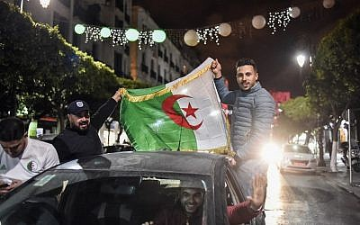 Algerians hold a national flag as they celebrate on an Algiers street on March 11, 2019, after President Abdelaziz Bouteflika announced his withdrawal from a bid for another term in office. (RYAD KRAMDI / AFP)