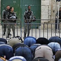 Muslim worshipers pray in front of a barrier after Border Police closed one of the entrances to the Temple Mount compound in the Old City of Jerusalem, which houses the Al-Aqsa Mosque, on March 12, 2019. (Ahmad Gharabli/AFP)