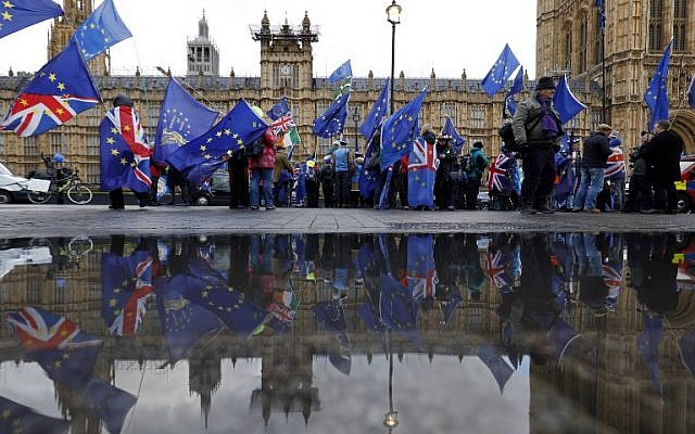 Anti-Brexit supporters wave flags as they demonstrate outside the Houses of Parliament in London on March 12, 2019. (Tolga Akmen/AFP)