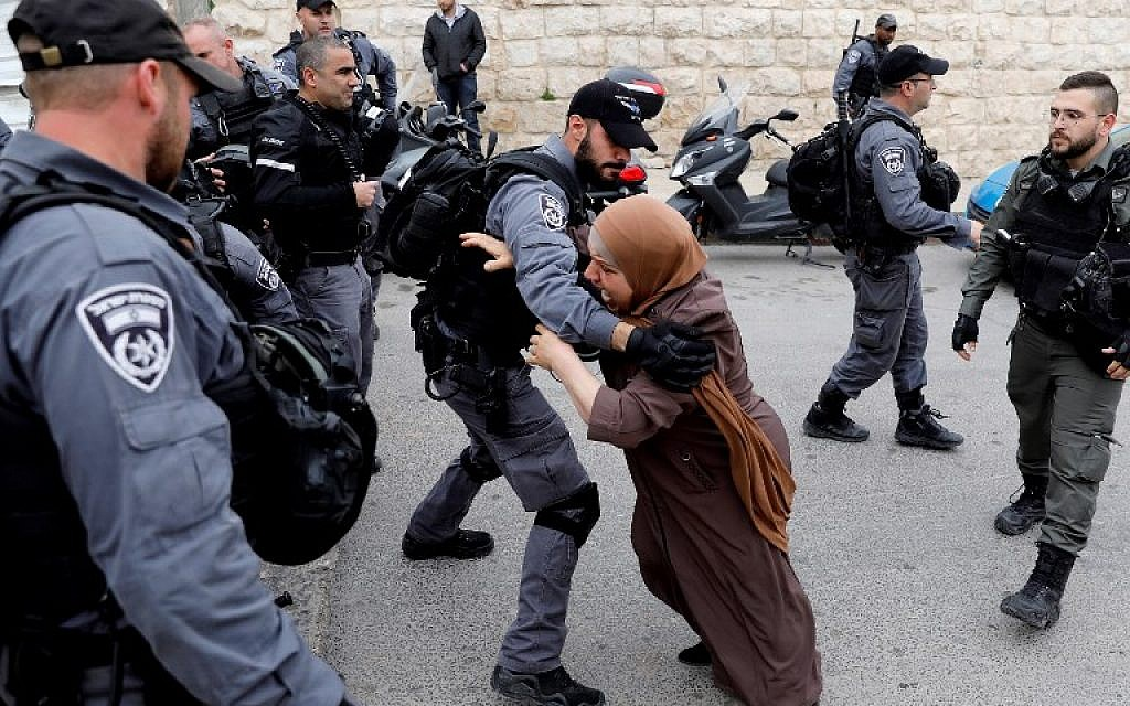 An Israeli policeman holds back a Palestinian woman outside the Old City in Jerusalem after police closed the entrance to al-Aqsa mosque compound on the Temple Mount following a firebomb attack on a police post at the site, on March 12, 2019. (Ahmad Gharabli/AFP)