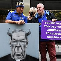 Protesters hold placards outside the County Court to hear the sentencing of Cardinal George Pell in Melbourne on March 13, 2019. - Disgraced Australian Cardinal George Pell was sentenced to six years in jail for child sex crimes in a Melbourne court on March 13 with a minimum period of three years and eight months to be served. (William WEST / AFP)