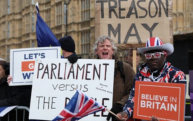 Protesters carry placards and shout slogans as they gather near the Houses of Parliament in London on March 13, 2019 (ISABEL INFANTES / AFP)