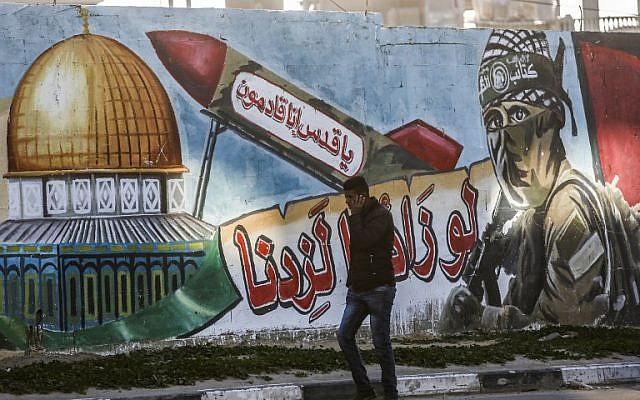 "A Palestinian man walks past a mural depicting a masked fighter of the Qassam Brigades, the armed wing of the Hamas movement, next to a missile with a caption reading in Arabic ""Oh Jerusalem, we are coming"" and the Dome of the Rock, in a street in Rafah in the southern Gaza Strip on March 14, 2019. (Photo by SAID KHATIB / AFP)"