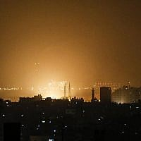 The sky above buildings in the Gaza Strip glows orange during an Israeli air strike in Gaza City early on March 15, 2019 after 2 missiles were fired at Tel Aviv. (Mahmud Hams/AFP)