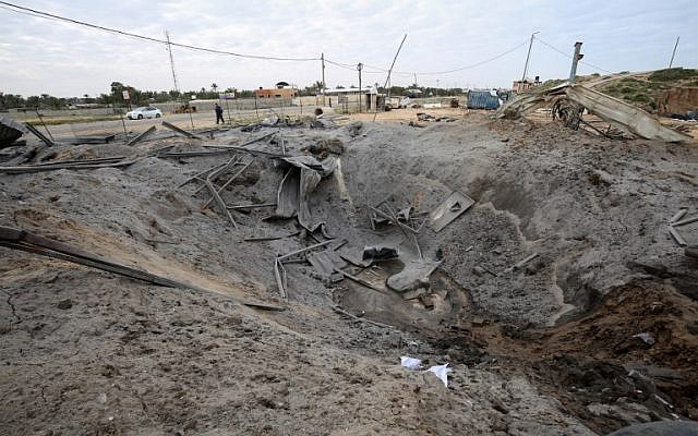 A Palestinian man walks past a crater on the ground following an Israeli air strike targeting a site belonging to Gaza's terror group Hamas, in Khan Yunis in the southern Gaza Strip, March 15, 2019. Israel struck Gaza terror targets after 2 rockets were fired at Tel Aviv from Gaza. (Said Khatib/AFP)