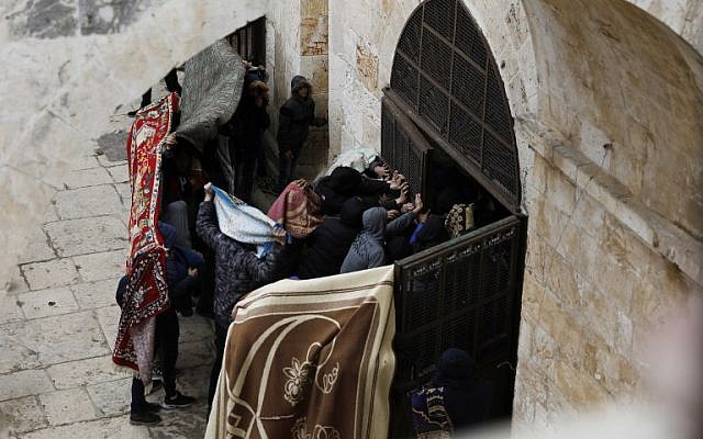Palestinians break a door of the Gate of Mercy on the Temple Mount in Jerusalem's Old City on March 15, 2019. (Ahmad Gharabli/AFP)