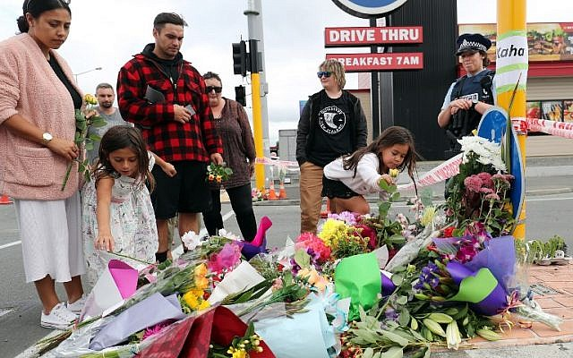 Residents place flowers at the police cordon as police continue to search the area close by the Linwood Ave Mosque in Christchurch, New Zealand, on March 16, 2019. (MICHAEL BRADLEY / AFP)