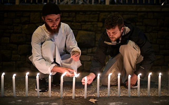 Well-wishers light 49 candles as they pay respects to victims outside the hospital in Christchurch on March 16, 2019, after a deadly shooting attack at two mosques in the city the previous day. (Anthony Wallace/AFP)
