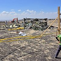 A boy looks as forensic investigators comb the ground for DNA evidence near a pile of twisted airplane debris at the crash site of an Ethiopian airways operated Boeing 737 MAX aircraft on March 16, 2019 at Hama Quntushele village near Bishoftu in Oromia region. (TONY KARUMBA / AFP)