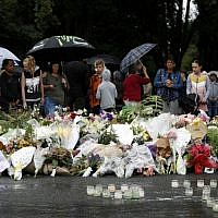 People gather in front of floral tributes at a makeshift memorial for victims of the March 15 mosque attacks, in Christchurch, New Zealand, on March 17, 2019. (Tessa BURROWS / AFP)