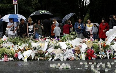 People gather in front of floral tributes at a makeshift memorial for victims of the March 15 mosque attacks, in Christchurch, New Zealand, on March 17, 2019. (Tessa Burrows/AFP)
