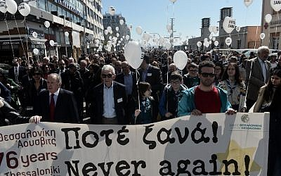 People hold a banner and balloons reading 'Never Again' as they walk toward the old railway station to mark the departure of the first train from Thessaloniki to the Auschwitz concentration camp in Poland on March 15, 1943, during a silent march in memory of Holocaust victims in Thessaloniki, on March 17, 2019. (Sakis MITROLIDIS / AFP)