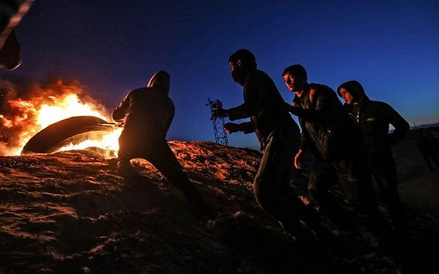 Palestinians take part in a night demonstration near the fence along the border with Israel, in Rafah in the southern Gaza Strip, on March 19, 2019. (Said Khatib/AFP)