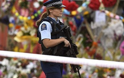 A policewoman patrols past a memorial wall outside the Linwood Mosque in Christchurch on March 21, 2019. (WILLIAM WEST / AFP)