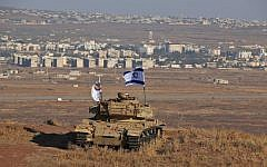Photo taken on October 18, 2017 shows an Israeli flag fluttering above the wreckage of an Israeli tank sitting on a hill in the Golan Heights and overlooking the border with Syria. (Photo by JALAA MAREY / AFP)