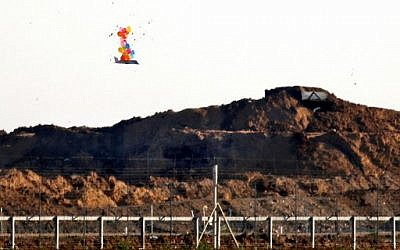 Illustrative: Balloons carry a makeshift drone-shaped object flying over the border with Israel east of Gaza City, after it was set loose by Palestinians during a protest by the fence, on March 22, 2019. (Said Khatib/AFP)