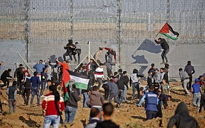 Palestinians wave Palestinian flags as they try to climb the security fence on the border between Israel and the Gaza Strip, east of Gaza City, on March 22, 2019. (Said Khatib/AFP)