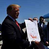 US President Donald Trump shows a map which he said indicates the end of ISIS, as he arrives at Palm Beach International Airport in Florida on March 22, 2019. (Photo by Nicholas Kamm / AFP)