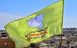 A picture taken on March 23, 2019 shows the US-backed Syrian Democratic Forces' (SDF) flag atop a building in the Islamic State group's last bastion in the eastern Syrian village of Baghouz after defeating the jihadist group (Giuseppe CACACE / AFP)