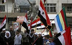 Residents of the Golan Heights wave Syrian and Druze flags as they gather in front of a portrait of Syrian President Bashar Assad during a protest against US President Donald Trump's recognition of Israeli sovereignty over the contested area, in the town of Majdal Shams, on March 23, 2019. (Jalaa Marey/AFP)