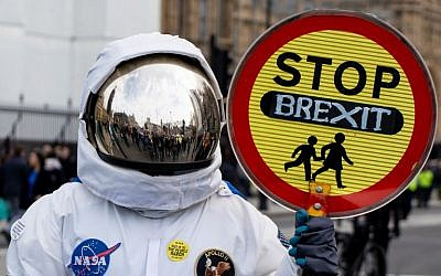 A person dressed as an astronaught holding a school traffic crossing sign reading 'Stop Brexit' joins a march and rally organised by the pro-European People's Vote campaign for a second EU referendum in central London on March 23, 2019. (Niklas HALLE'N / AFP)