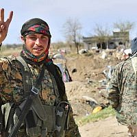 A picture taken on March 23, 2019, shows a fighter of the US-backed Kurdish-led Syrian Democratic Forces (SDF) flashing the V for victory sign in the fallen Islamic State group's last bastion in the eastern Syrian village of Baghuz after defeating the jihadist group. (GIUSEPPE CACACE / AFP)
