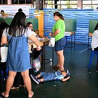 A child lies on the floor as voters cast their ballots at a polling station in Bangkok on March 24, 2019, during Thailand's general election. (Jewel SAMAD / AFP)