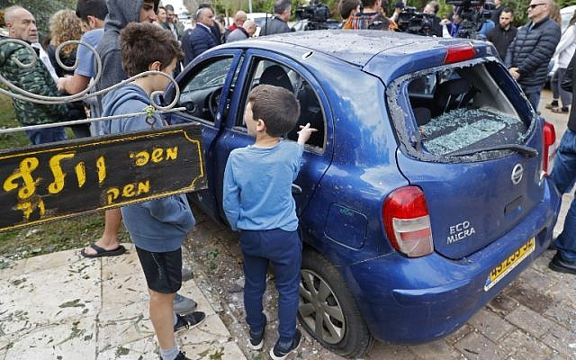 People gather around a damaged car next to the home of the Wolf family in the central Israeli village of Mishmeret, after it was hit by a rocket launched from Gaza, on March 25, 2019. The sign at left reads, 'Wolf family.' (Jack Guez/AFP)