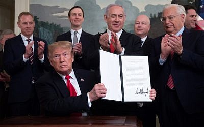 US President Donald Trump holds up a signed Proclamation on the Golan Heights, alongside Prime Minister Benjamin Netanyahu, in the Diplomatic Reception Room at the White House in Washington, DC, March 25, 2019.  (SAUL LOEB / AFP)