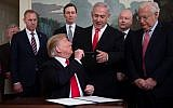US President Donald Trump hands his pen to Prime Minister Benjamin Netanyahu after signing a Proclamation on the Golan Heights in the Diplomatic Reception Room at the White House, March 25, 2019. (SAUL LOEB/AFP)