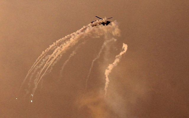An Israeli helicopter shoots flares over the Gaza Strip hours after a rocket from the Palestinian enclave hit a house near Tel Aviv and wounded seven people, leading to fears of a severe escalation, on March 25, 2019. (Mohammed Abed/AFP)