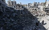 A picture taken on March 26, 2019, shows Palestinians gathering next to the rubble of a building in Gaza City, after Israeli air strikes hit dozens of sites across the Strip overnight in response to rocket fire from the Palestinian enclave. (MAHMUD HAMS / AFP)