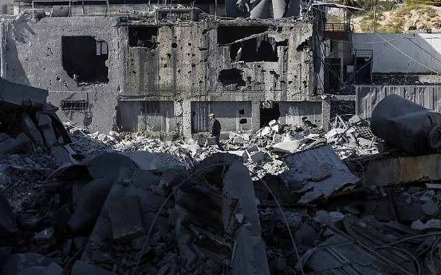 A picture taken on March 26, 2019, shows a Palestinian man making his way through the rubble of a building in Gaza City, after Israeli air strikes hit dozens of sites across the Strip overnight in response to rocket fire from the Palestinian enclave. (Mahmud Hams/AFP)