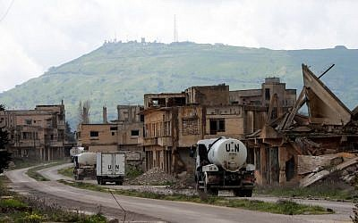 A convoy of UN vehicles drive through damaged buildings in the Syrian town of Quneitra, in the Golan Heights on March 26, 2019. (Louai Beshara/AFP)
