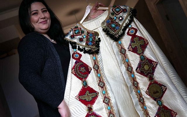 Iraqi Kurdish artist Shanaz Jamal, 40, poses with one of her embroidered robes ornated with religious symbols of communities of Iraq's multi-ethnic north, in Arbil, the capital of the Kurdish autonomous region, on March 27, 2019. (Photo by SAFIN HAMED / AFP)