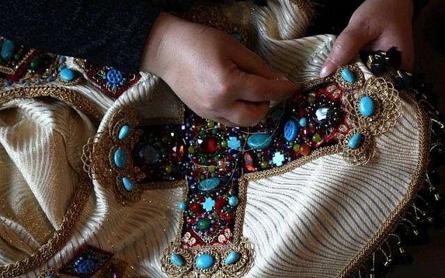 Iraqi Kurdish artist Shanaz Jamal, 40, embroiders a robe ornated with a big cross, one of the religious symbols of communities living in  Iraq's multi-ethnic north, in Arbil, the capital of the Kurdish autonomous region, on March 27, 2019. (Photo by SAFIN HAMED / AFP)