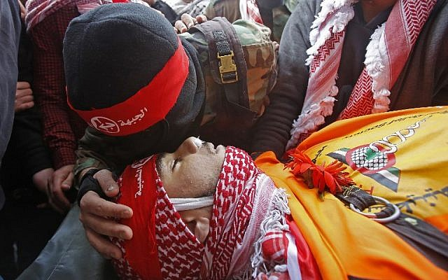 A member of the Popular Front for the Liberation of Palestine terror group kisses the head of Sajid Muzher, 17, after he was reported killed by Israeli fire during clashes in the Dheisheh refugee camp near the West Bank city  of Bethlehem, during his funeral on March 27, 2019. (Musa Al Shaer/AFP)