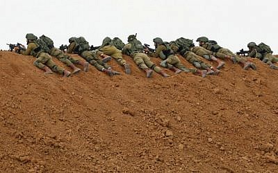 In this file photo taken on March 30, 2018 Israeli soldiers keep position as they lie prone over an earth barrier along the border with the Gaza Strip in the southern Israeli kibbutz of Nahal Oz as Palestinians demonstrate on the other side commemorating Land Day. (Jack Guez/AFP)