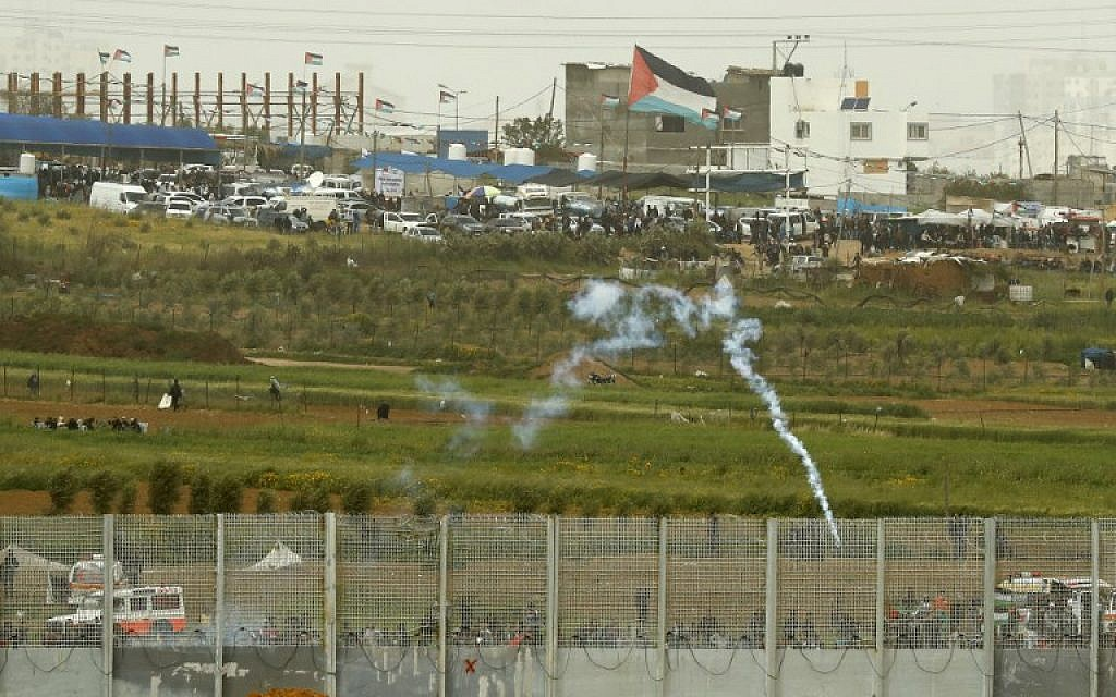 This picture taken on March 30, 2019, in Kibbutz Nahal Oz across the border from the Gaza Strip shows a tear gas canister falling among Palestinians near the security fence as they mark the first anniversary of the 'March of Return' protests. (Jack Guez/AFP)