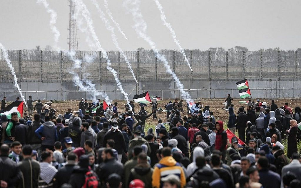 Tear gas canisters fall amongst Palestinians during a demonstration near the border with Israel, in Malaka east of Gaza City, on March 30, 2019 (Mahmud Hams/AFP)