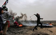 Illustrative: A Palestinian protester uses a slingshot to hurl a rock toward Israeli forces during clashes following a demonstration along the border with Israel in Malaka east of Gaza City on March 30, 2019. (Mahmud Hams/AFP)