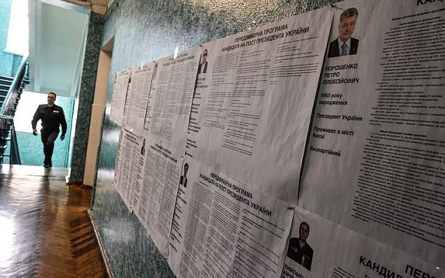 A security officer walks past voting information boards on candidates at a polling station in the center of Kiev on March 30, 2019 ahead of the Ukrainian presidential election on March 30. (Vasily Maximov/AFP)