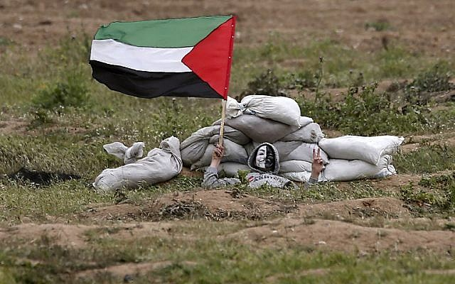 A Gazan protester waves a flag during clashes with Israeli forces on March 30, 2019. (MAHMUD HAMS / AFP)