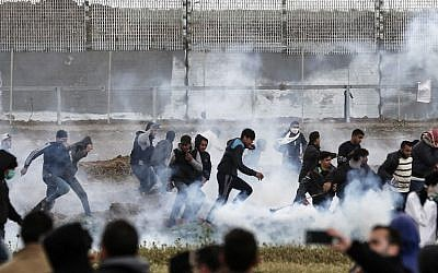 Palestinian protesters run for cover from tear gas canisters fired by Israeli forces during clashes amid a mass demonstration marking the first anniversary of the March of Return protests, near the border with Israel east of Gaza City on March 30, 2019. (Mahmud Hams/AFP)
