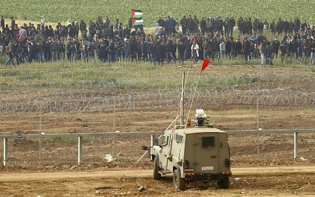 "This picture taken on March 30, 2019 from the southern Israeli kibbutz of Nahal Oz across the border from the Gaza Strip, shows Israeli military vehicles keeping position at the border fence, as Palestinians, waving national flags, demonstrate to mark the first anniversary of the ""March of Return"" protests. (Jack Guez/AFP)"
