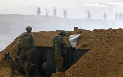 "Israeli soldiers gather at a position over an earth barrier along the border with the Gaza Strip near the southern Israeli kibbutz of Nahal Oz on March 30, 2019, as Palestinians (background) protest to mark the first anniversary of the ""March of Return"" protests. (Jack Guez/AFP)"
